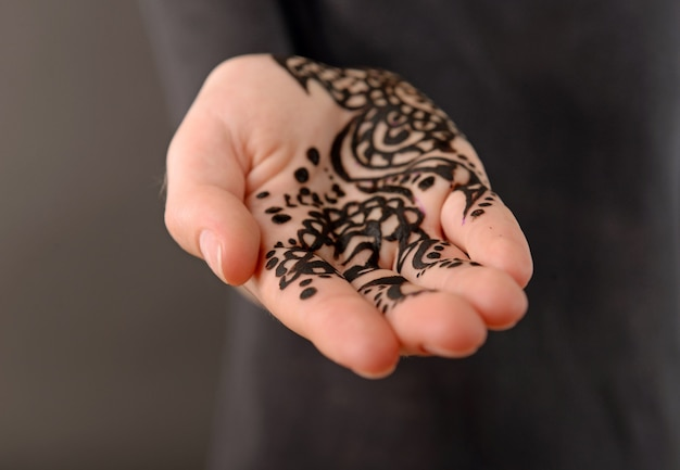 Nahaufnahmebild von henna auf weiblicher hand auf dunkelheit