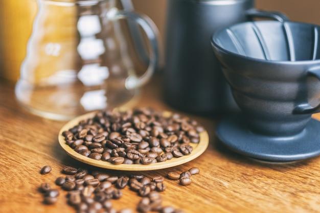 Nahaufnahmebild von kaffeebohne und kaffeetropf auf holztisch