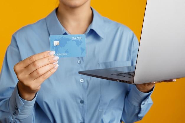 Nahaufnahmebild von laptop und einkaufskreditkarte in den händen der frau.