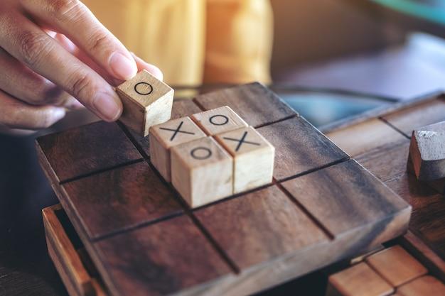 Nahaufnahmebild von leuten, die hölzernes tic tac toe-spiel oder ox-spiel spielen