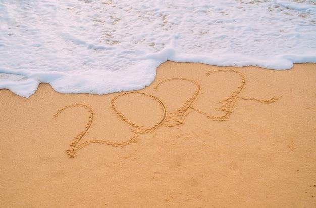 Nahaufnahmebild von meereswellen, die 2022 neujahrszahlen vom sand am strand waschen. konzept von neujahr, weihnachten und reisen in den winterferien