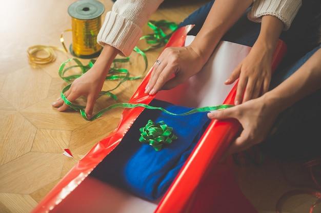 Nahaufnahmebild von mutter und tochter, die weihnachtsgeschenk machen und pullover in geschenkpapier einwickeln