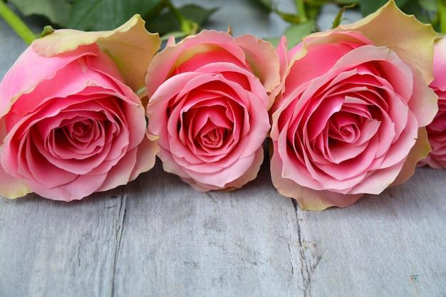 Nahaufnahmebild von rosa rosen auf einer holzoberfläche
