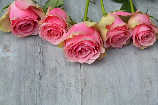 Nahaufnahmebild von rosa samtrosen auf einer holzoberfläche