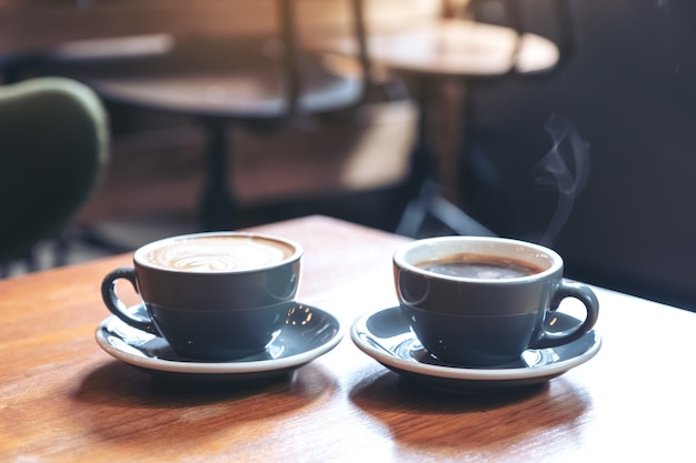 Nahaufnahmebild von zwei blauen tassen des heißen lattekaffees und des americano-kaffees auf weinlesetisch im weinlesetisch im café