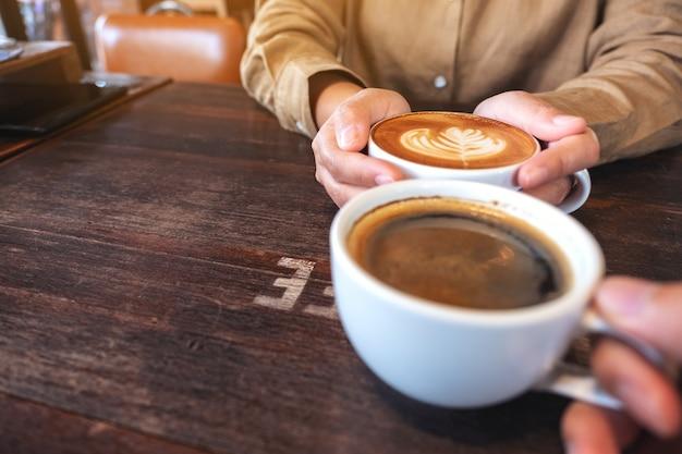 Nahaufnahmebild von zwei personen, die weiße tassen heißen kaffees auf holztisch im café halten