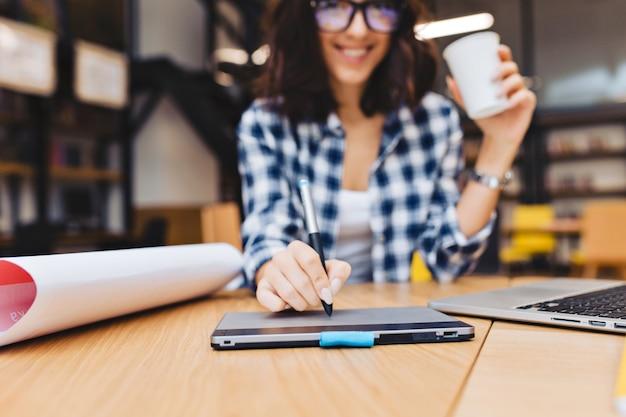 Nahaufnahmebildhand der jungen brünettenfrau, die auf tisch in der bibliothek umgibt, um arbeitssachen zu umgeben. laptop, kreative arbeit, grafikdesign, freiberufler, kluger student.