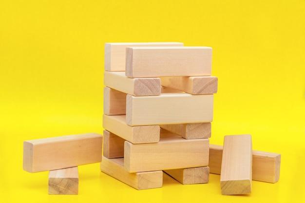Nahaufnahmeblöcke des holzes auf gelbem hintergrund mit einer kopie des raumes. strategiespiel als businessplan für teamarbeit