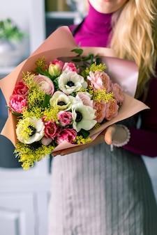Nahaufnahmeblumen in der hand. florist arbeitsplatz. frau, die einen blumenstrauß mit rosen, chrysantheme, nelke und anderen blumen arrangiert. ein lehrer für floristik in meisterklassen oder kursen.