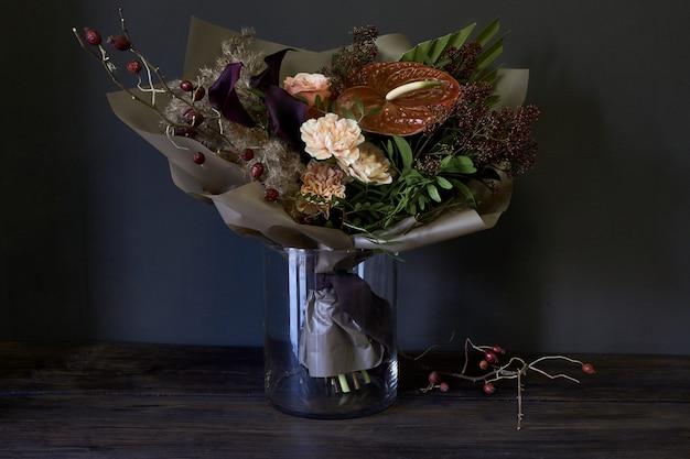 Nahaufnahmeblumenstrauß in einem glasvase verziert in der weinleseart auf einem dunklen hintergrund