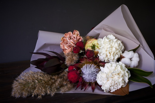 Nahaufnahmeblumenstrauß verziert in der weinleseart auf einem dunklen hintergrund