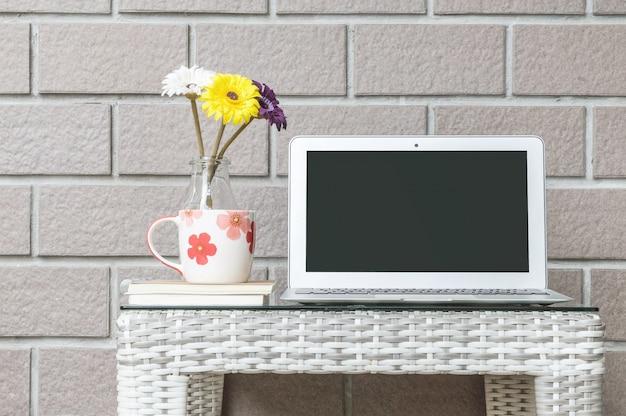 Nahaufnahmecomputer auf hölzerner webartentabelle und brauner backsteinmauer masern hintergrund