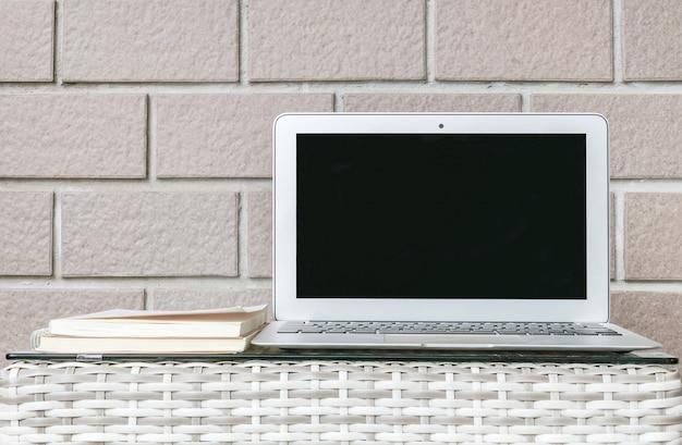 Nahaufnahmecomputer auf unscharfer hölzerner webartentabelle und brauner backsteinmauer masern hintergrund