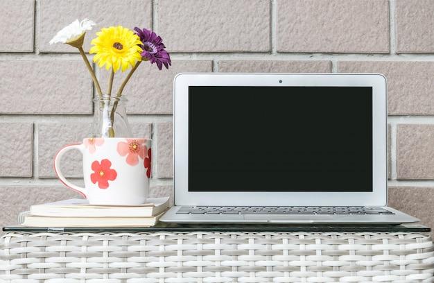 Nahaufnahmecomputer auf unscharfer hölzerner webarttabelle und braunem backsteinmauerbeschaffenheitshintergrund