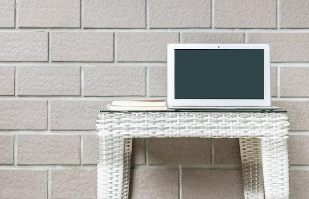 Nahaufnahmecomputer auf unscharfer hölzerner webarttabelle und brauner backsteinmauer