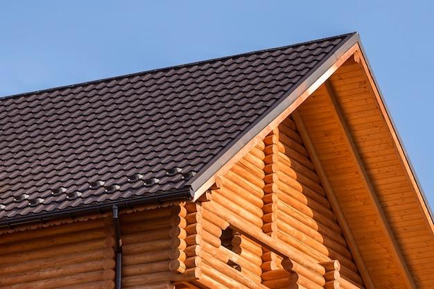 Nahaufnahmedetail der neuen modernen hölzernen warmen ökologischen häuschenhausspitze mit geschichtetem braunem dach und hölzernen abstellgleisen auf blauem himmel professionell erledigte zimmerei und bauarbeit.