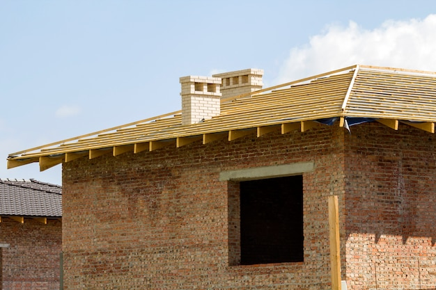 Nahaufnahmedetail des hölzernen dachs des neuen backsteinhauses mit zwei weißen kaminen im bau. holzrahmen von natürlichen materialien gegen hellen himmel. professionelles bau- und umbaukonzept.