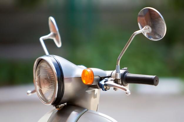 Nahaufnahmedetail des neuen weißen glänzenden motorrades mit rundem scheinwerfer