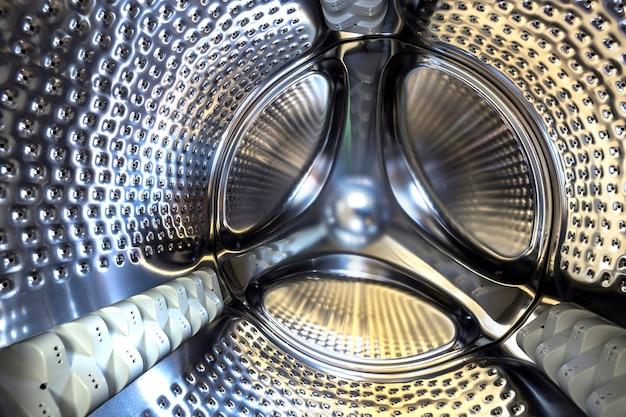 Nahaufnahmedetail, rostfreie trommel des modernen waschmaschineninnenraums. abstraktes silbernes glänzendes oberflächendesign.