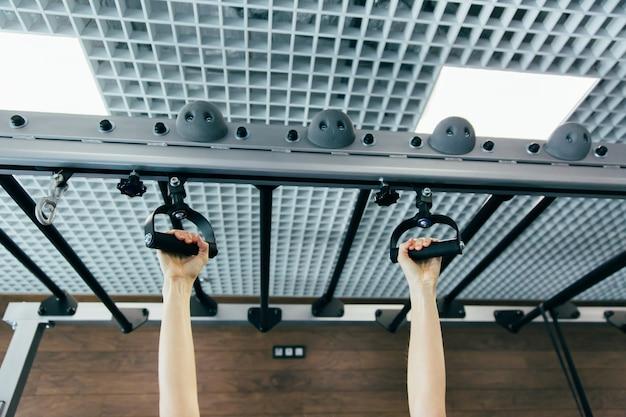 Nahaufnahmedetail von den weiblichen händen, die eine klimmzüge in einer turnhalle halten