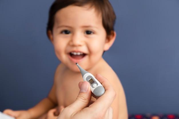 Nahaufnahmedoktor, der einen thermometer hält