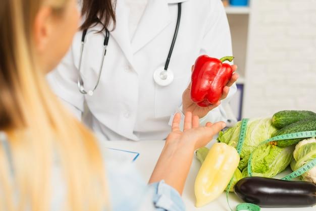 Nahaufnahmedoktor und -patient mit gemüse
