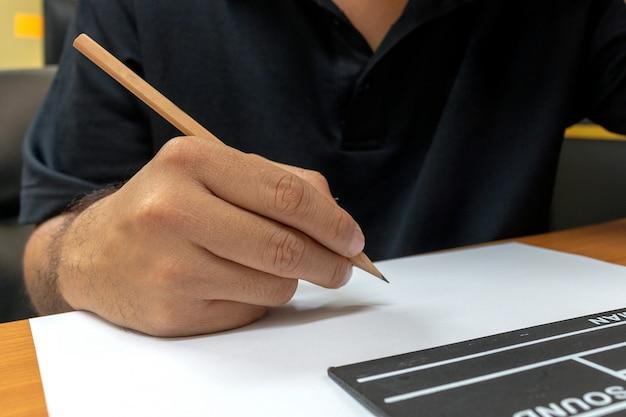 Nahaufnahmedrehbuchautoren mit filmscharnierventil auf tabelle im büro
