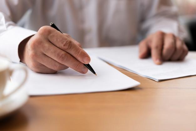 Nahaufnahmeerwachsener, der einen vertrag im büro unterzeichnet