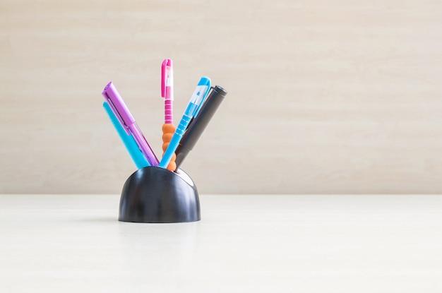 Nahaufnahmefarbstift mit dem schwarzen keramischen schreibtisch sauber auf hölzernem schreibtisch