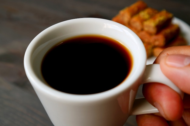 Nahaufnahmefinger, die eine tasse türkischen kaffee mit verschwommenem baklava-gebäck im hintergrund halten