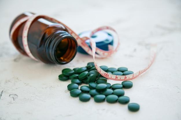 Nahaufnahmeflasche der grünen spirulina-pillen mit einem maßband. super food konzept. spirulina nahrungsergänzungsmittel.