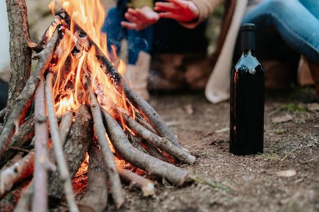 Nahaufnahmeflasche wein und feuer mit nicht erkennbaren frauen, die ihre hände wärmen.