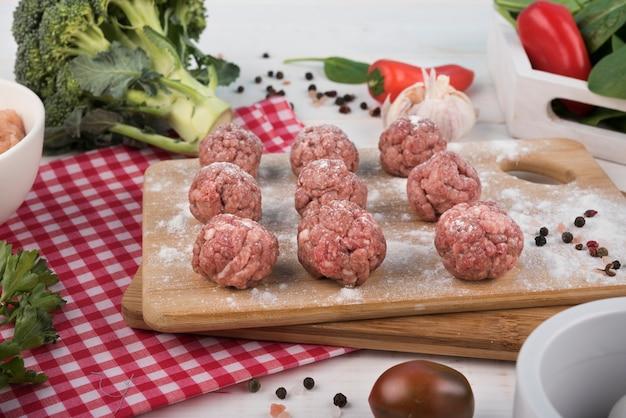 Nahaufnahmefleischklöschen auf hölzernem brett und brokkoli