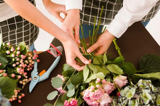 Nahaufnahmefloristen, die blumenstrauß mit rosen machen