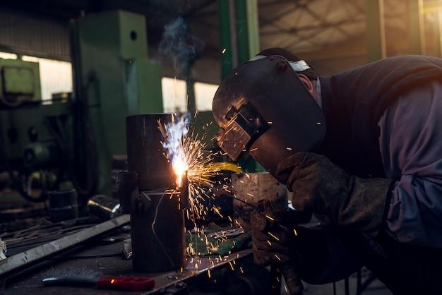 Nahaufnahmefokus-seitenansicht des professionellen maskengeschützten schweißers, der an der metallskulptur in der werkstatt arbeitet.