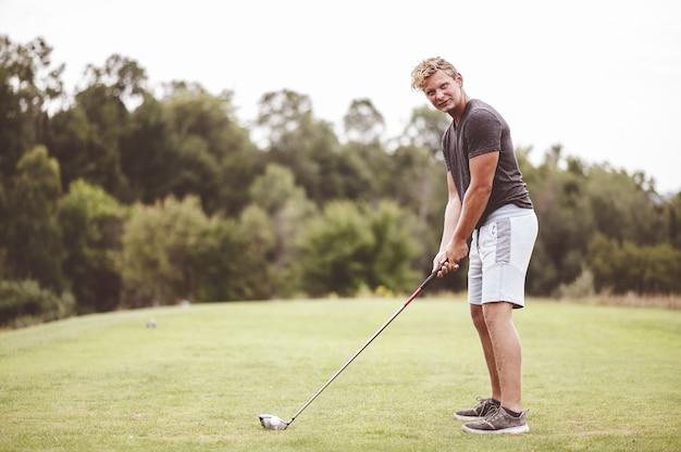Nahaufnahmefokusporträt eines jungen mannes, der golf spielt