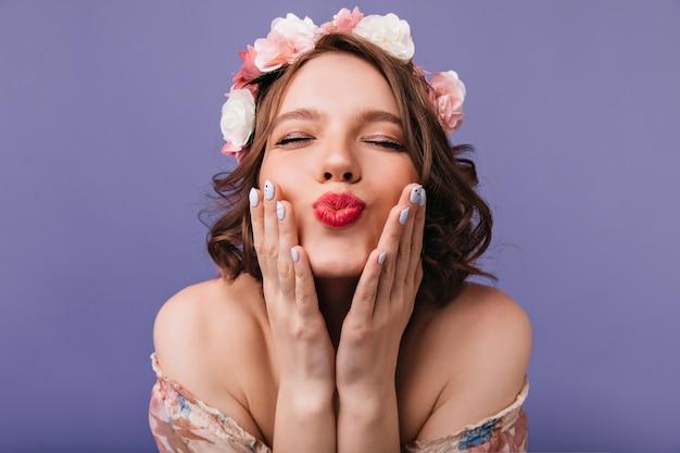 Nahaufnahmefoto der attraktiven europäischen dame mit rosen im kurzen haar. glückliches weißes mädchen im kranz, der aufwirft.