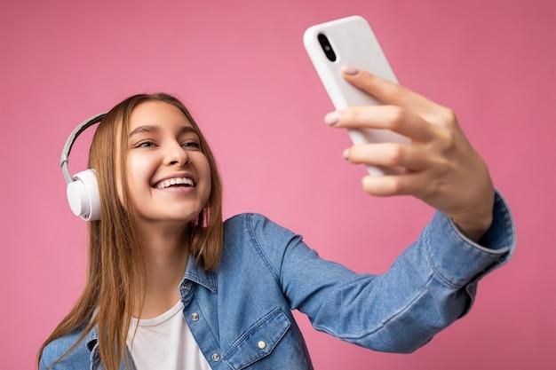 Nahaufnahmefoto der attraktiven glücklichen lächelnden jungen blonden frau, die stylisches hemd der blauen jeans trägt und