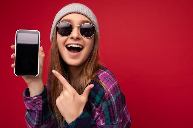Nahaufnahmefoto der attraktiven lächelnden positiven jungen blonden frau, die stilvolles lila hemd trägt und