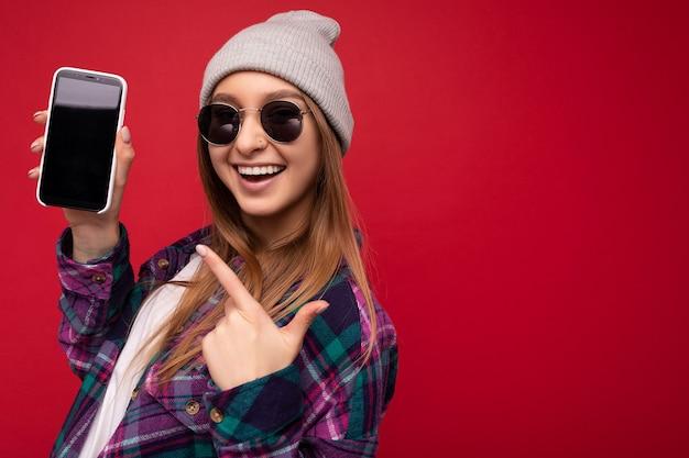 Nahaufnahmefoto der attraktiven lächelnden positiven jungen blonden frau, die stilvolles purpurrotes hemd trägt und