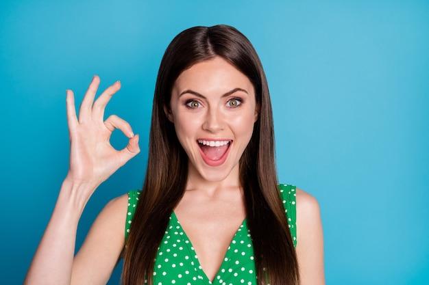 Nahaufnahmefoto der attraktiven lustigen dame, die charmant niedliche mädchenhafte gute laune zeigt, okey symbolhandarm, der zustimmungshaltung ausdrückt, tragen lässiges grün gepunktetes unterhemd isoliert blauer farbhintergrund