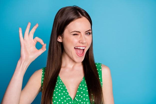 Nahaufnahmefoto der attraktiven lustigen dame, die charmant süße mädchenhafte stimmung zeigt, okey symbol hand arm blinkendes auge, das zustimmung ausdrückt, tragen lässiges grün gepunktetes unterhemd isoliert blauer farbhintergrund