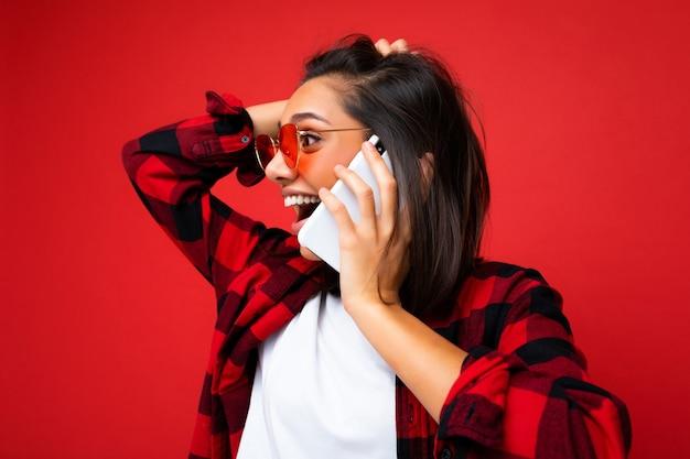 Nahaufnahmefoto der attraktiven positiv überraschten jungen brunettefrau, die stilvolles rotes hemd weiß trägt