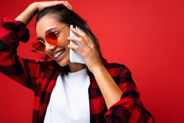 Nahaufnahmefoto der attraktiven positiven lächelnden jungen brunettefrau, die stilvolles rotes hemd weiß trägt