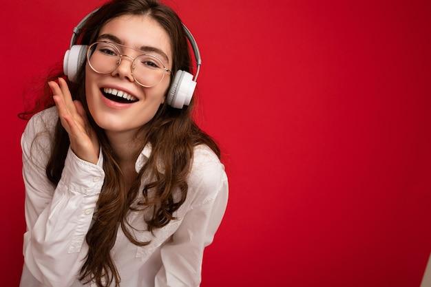 Nahaufnahmefoto der attraktiven positiven lächelnden jungen brunettefrau, die weißes hemd und optisches trägt