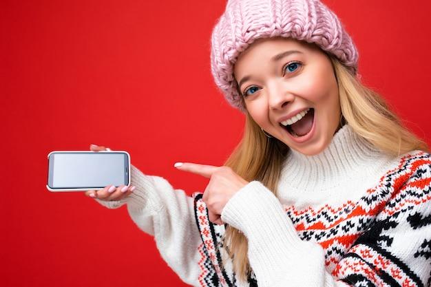 Nahaufnahmefoto der attraktiven überraschten lächelnden jungen blonden frau, die warme strickmütze und winter trägt
