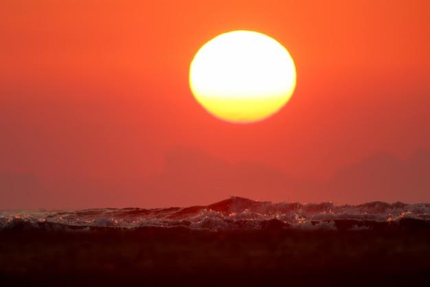 Nahaufnahmefoto der aufsteigenden weißgelben sonne über dem stürmischen schwarzen meer