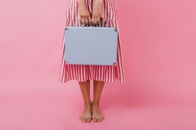 Nahaufnahmefoto der blauen aktentasche in den händen des schlanken mädchens im midi-langen kleid.