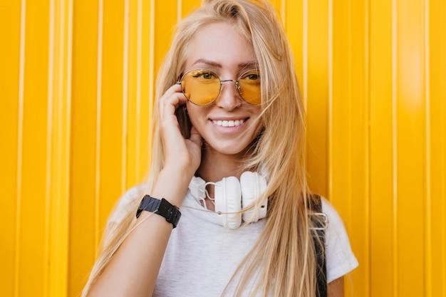 Nahaufnahmefoto der charmanten jungen dame, die auf gelbem hintergrund mit schönem lächeln aufwirft. fröhliches langhaariges mädchen in kopfhörern, das glückliche gefühle ausdrückt.