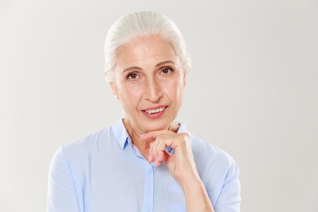 Nahaufnahmefoto der eleganten fröhlichen alten dame, die ihr kinn hält